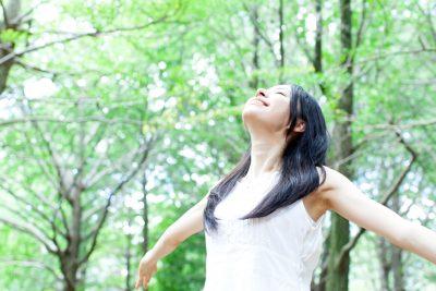 森で深呼吸をしている女性